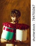 Small photo of bearded macho happy man, brutal caucasian hipster with moustache with muscular torso, chest and body, holds red pink rose flowers in box as present on golden background