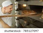 cheerful male baker smiling... | Shutterstock . vector #785127097