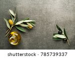 Small photo of Olive oil and olive branch on gray background