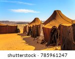 Small photo of Nomad tents in the middle of the desert with mountains in the background on a sunny day