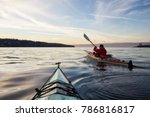 Stock photo adventure man on a sea kayak is kayaking during a vibrant and colorful winter sunset taken in 786816817
