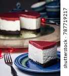 Small photo of Piece of cheesecake with three colored layers is laying on blue plate. Red strawberry jelly on the top, Oreo layer on the bottom.