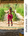 Small photo of LUANG PRABANG, LAOS - JANUARY 11, 2017: Girl swinging on a swing. Vertical.