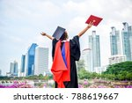 Small photo of back view of graduate student asian woman hug future and look up to copy space, she wear graduation cap and gown