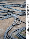Small photo of beautiful curvy power lines electrical hook ups on ground texture