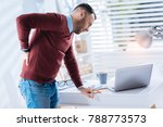 Small photo of Awful backache. Young emotional exhausted worker of a big company leaning towards the table while suffering from an awful backache and wishing to go home