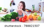 Small photo of Young woman sitting near desk in the kitchen