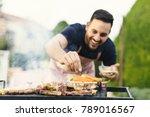 Smiling Man Seasoning Meat On...