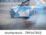 Small photo of Drifting car in smoke from burning tires on the track in motion