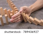 Small photo of hand stopping wooden block domino. concept prevent and solution.