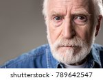 Small photo of Close up of severe hoary man staring at camera. Copy space in left side. Isolated on grey background