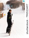 Small photo of Snowboarder dragging the snowboard and equipment over the snow