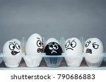 Small photo of Faces on chicken eggs in the form of facial expressions, reflecting emotions. The concept of racism, misunderstanding, a barrier in relations, denial of society. Barriers between people, prejudice.