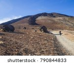 Small photo of desert volcanic landscape with lonely hiker climbing on volcano pico del teide with Huevos del Teide (Eggs of Teide) accretionary lava balls on clear blue sky background
