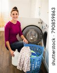 Small photo of The young cheerful woman sitting near washing machine in the room and holding abstergent in hand