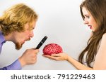 Small photo of Woman and man looking at human brain model using magnifying glass for closer look.