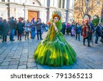 Small photo of VENICE, ITALY, FEBRUARY 25, 2017: Female in a costume is strolling through streets of Venice during the world famous carnival. People are showing off in beautiful dresses accompanied with a mask.