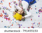 Small photo of Little girl child cute and beautiful with multi-colored confetti on the floor happy is happy in a paper crown Princess