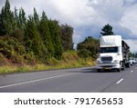 Small photo of White Bonnet Big rig day cab semi truck with spoiler on the roof moving with step down semi trailer transporting black plastic pipes on green wide multiline highway with trees on roadside
