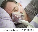 Small photo of Man Lying On Bed With Sleeping Apnea And CPAP Machine