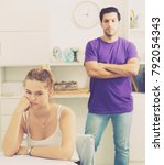 Small photo of Young woman sitting at home table offended after quarrel with husband