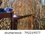 welder makes a fence in the... | Shutterstock . vector #792219577