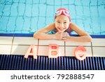 Happy kid in swimwear looking...