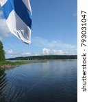 Small photo of A vertical or portrait format photo of the Finnish flag flying from the aft of a boat as it crosses a clear blue Finnish lake in Finland.