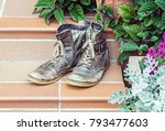 pair of old worn out boots at... | Shutterstock . vector #793477603