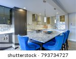 Small photo of Well appointed kitchen features a large island topped with a gray quartzite countertop and flanked by blue tufted dining chairs with silver nailhead trim.