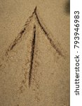 Small photo of Hand drawn arrow in the ocean sand beach.