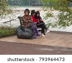 Small photo of VIETNAM, HANOI - DECEMBER 30, 2017. Two girlfriends of schoolgirls sit beside on a bench and do selfie, and next there sits an old woman in dirty clothes in the background of a park with a lake