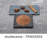 Small photo of Cocoa powder, cinnamon stick and star anis on concrete
