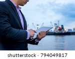 Small photo of Internet of Things, Smart Businessman use tablet at port import and export shipping