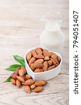Small photo of Almond milk in bottle with almond on wooden background.