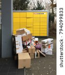 Small photo of Nuremberg, Bavaria / Germany - 01 15 2018: Pile of return parcels and packages from online shopping stores in front of a 24-hour self-service parcel storage station from DHL, so called Packstation