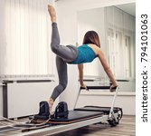 Small photo of Woman exercising on Pilates reformer