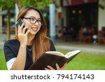 a girl in a park holding a book | Shutterstock . vector #794174143