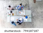 Small photo of Success achieved. Architects and Engineers Team gesturing and relaxing while sitting at desk in construction site. Business people Trust in Team Start up project Contractor after meeting a good deal.
