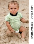 Closeup of a cute baby boy sitting on the beach - stock photo