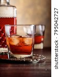 Small photo of Glass of scotch whiskey and natural ice on old wooden table.