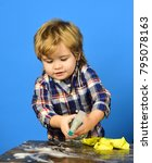 Small photo of Child with busy face holds spray above table. Kid near wooden table with rag and foam on. Boy in checkered shirt on blue background. Parents little helper concept.