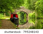 Small photo of A scene of serenity and reflections, a narrowboat is seen on the still canal waters in the heartland of England, along with a stone arched bridge.