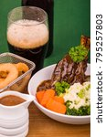 Small photo of Lamb Shank Dinner. Traditional St Patrick's Day Lamb Shank served with Colcannon, Stout battered onion rings and a glass of Irish Stout.