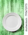 white empty dish on green wood... | Shutterstock . vector #795672973