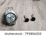 Small photo of Wedding accessories on rustic brown wooden background. traditional idea composition. holiday concept. Side view. Cufflinks for groom. Stylish men's watch, accessory, business hours.