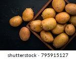 raw potatoes on a black wooden... | Shutterstock . vector #795915127