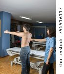 Small photo of Chiropractor doing a visual exploring, static, dynamic position, scoliosis, kyphosis. Dynamic evaluation of scapular tilt during an abduction
