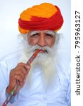 Small photo of JODHPUR, RAJASTHAN, INDIA - DECEMBER 17, 2017: Portrait of a man with long white mustache (whiskers) and beard and an orange turban in Mehrangarh fort