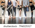 Small photo of Group of young sporty people standing at wall. Students taking a rest from fitness activity, time to recover strength, waiting for a lesson to start in loft studio, close up. Healthy lifestyle concept